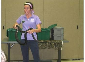 student intern at sandy creek handles snake