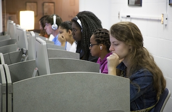 A diverse group of male and female students each sit at a Mac computer station in the BLC.